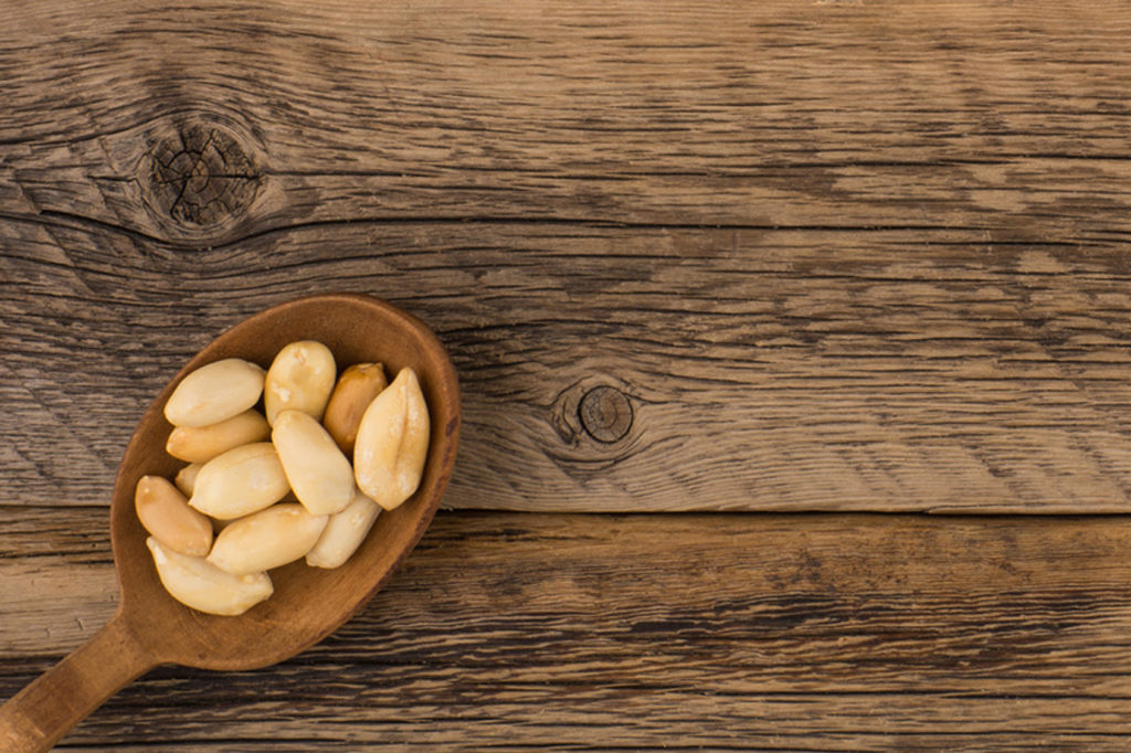 Peanuts in wooden spoon on an old wooden background.